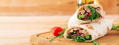 Tortillas wraps with chicken and vegetables on wooden background. Chicken burrito. Banner. Healthy food stock photo