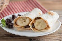 Tortillasjal med det jordnötsmör, russinet och bananen Arkivfoto