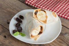 Tortillasjal med det jordnötsmör, russinet och bananen Arkivbild