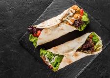 Tortillasjalar med grillad kött, nya grönsaker och sallad på svartstenbakgrund Sunt mellanm?l eller tagande-bortlunch Top besk?da royaltyfria bilder