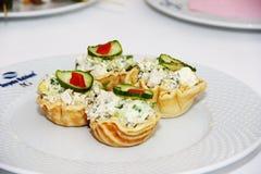 tortini con insalata ed il cetriolo verde sul piatto bianco fotografia stock