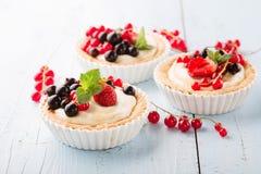 Tortini con le bacche crema e fresche Fotografia Stock