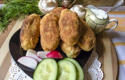 Tortini con le patate, i funghi e un aneto Immagini Stock