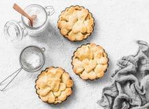 Tortini croccanti della mela della pasticceria dello shortcrust di disposizione piana nel piatto di cottura su fondo leggero, vis Fotografia Stock