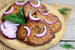 Tortini del fegato di pollo con la carota e la cipolla Tortini casalinghi del fegato di pollo fritto su un tagliere di legno fotografia stock libera da diritti