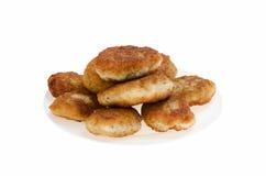 Tortini del pollo dell'alimento su un piatto su un fondo bianco fotografia stock