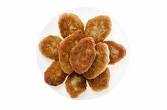 Tortini del pollo dell'alimento su un piatto su un fondo bianco Immagini Stock Libere da Diritti