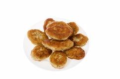 Tortini del pollo dell'alimento su un piatto su un fondo bianco immagini stock
