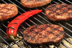 Tortini dell'hamburger del BBQ e griglia di Chili Pepper On The Hot Immagine Stock Libera da Diritti