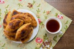 Tortini russi con cavolo su un piatto e una tazza di tè sul Fotografie Stock Libere da Diritti