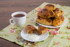 Tortini russi su un piatto e su una tazza di tè sul grumo variopinto Immagini Stock