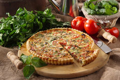 Tortino salato mediterraneo. Mediterranean savory pie on rustic wooden cutting board with vegetables royalty free stock photo