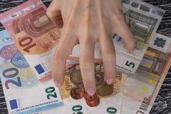 Torto da ingordigia, dalla mano dei rastrelli della donna su un mazzo di euro note e dalle monete a voi stesso fotografie stock libere da diritti