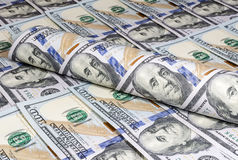 Torto in un tubo le banconote di cento dollari su un fondo di cento banconote in dollari Immagine Stock Libera da Diritti