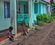 Tortuguero, Costa Rica Child at Home. Small boy and bicycle sitting at his colorful aqua colored home and dirt road in the small town of Tortugurero, Costa Rica Stock Photo
