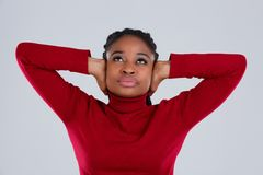 Tortured girl, Afro-American appearance, with displeased look looking up with hands over ears. Tortured young girl, Afro-American appearance, dressed in red Royalty Free Stock Photography