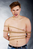 Tortured man tied with a rope. Royalty Free Stock Images