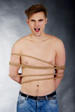 Tortured man tied with a rope. Tortured shirtless man tied with a rope Royalty Free Stock Images