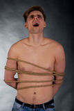 Tortured man tied with a rope. Tortured shirtless man tied with a rope Stock Photography