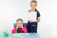 Tortured schoolgirl received five. Two girls play school teacher and student Stock Photo