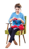 Tortured young girl in a  sweater sits on a chair with a red ball of yarn and knitting a scarf and Spitz. Tired. White background. Tortured young girl in a blue Royalty Free Stock Photos