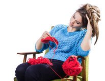Tortured young girl in a  sweater sits on a chair with a red ball of yarn and knitting a scarf and Spitz. Tired. White background. Tortured young girl in a blue Stock Photos