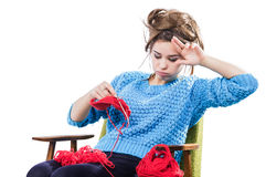 Tortured young girl in a  sweater sits on a chair with a red ball of yarn and knitting a scarf and Spitz. Tired. White background. Tortured young girl in a blue Royalty Free Stock Image