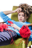 Tortured young girl in a  sweater sits on a chair with a red ball of yarn and knitting a scarf and Spitz. Tired. White background. Royalty Free Stock Image