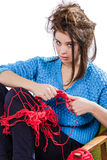 Tortured young girl in a  sweater sits on a chair with a red ball of yarn and knitting a scarf and Spitz. Tired. White background. Tortured young girl in a blue Royalty Free Stock Photography