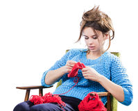 Tortured young girl in a  sweater sits on a chair with a red ball of yarn and knitting a scarf and Spitz. Tired. White background. Tortured young girl in a blue Royalty Free Stock Images