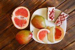 Torty, plasterki grapefruitowy i bonkrety k?amaj? w bia?ym talerzu na drewnianym stole robi? sosnowe deski Bufet w autentyczny na zdjęcia stock