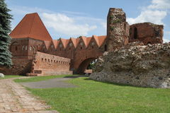 Torun Castle. In Poland on a sunny day with clouds and a view of some walls and a gate Stock Photography