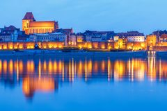 Torun at night, medieval Old Town reflected in Vistula river, Poland. Europe. royalty free stock images