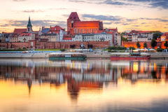 Torun old town reflected in Vistula river at sunset royalty free stock images