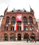 Torun, Poland. Famous old town building of Artus Court (Dwor Artusa) with Polish national emblem and flags Stock Photos