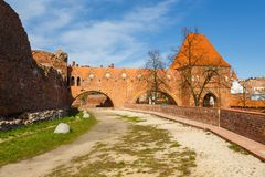 Street in old town with tower of Teutonic knights castle, Torun, Poland. Torun, Poland- 05 April 2014: The sewage tower of the Torun Castle. Teutonic Knights Stock Image