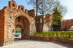 Street in old town with tower of Teutonic knights castle, Torun, Poland. Torun, Poland- 05 April 2014: The sewage tower of the Torun Castle. Teutonic Knights Royalty Free Stock Photography