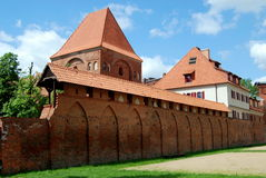 Torun, Poland: City Defense Walls & Tower. 13th century brick Gdanisko Tower stands just inside the old medieval city defense walls with their covered ramparts Royalty Free Stock Photos