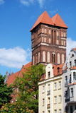 Torun, Poland: St James Church. Soaring west front of twin-towered brick Church of St. James looms high above surrounding 18th century baroque houses in the New Stock Photography