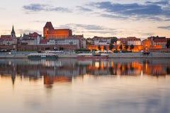 Torun reflekterade den gamla staden i Vistula River på solnedgången Arkivbild