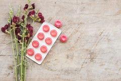 Tosa la pastilla de la garganta dolorida colorida y el flowerw en la tabla foto de archivo