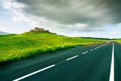 Toscânia, exploração agrícola e estrada na paisagem rural perto de Volterra na mola, Itália. Fotografia de Stock