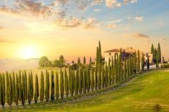Toscânia no pôr do sol - estrada do campo com árvores e casa Fotos de Stock