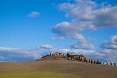 Toscaanse Boerderij op een heuvel met blauwe hemel en wolk Royalty-vrije Stock Foto's
