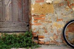 Toscaanse scène met baksteen, houten deur, installatie en fiets Stock Foto