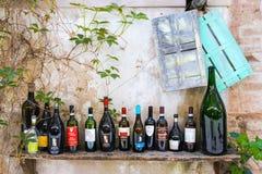 Toscaanse wijnflessen in rij op een plank stock afbeelding