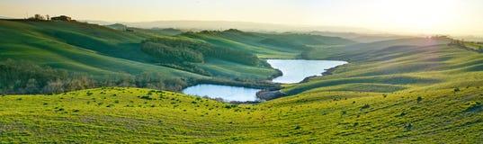 Toscana, paisaje rural en la puesta del sol, Italia. Lago y campos verdes Foto de archivo libre de regalías