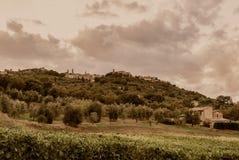 Toscanië - de Stad van de Heuveltop van Mantalcino zoals die van een hieronder Landbouwbedrijf wordt gezien royalty-vrije stock afbeelding