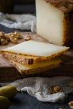Toscano italiano del pecorino del queso duro cortado en el tablero de madera con las aceitunas verdes y las nueces Imágenes de archivo libres de regalías