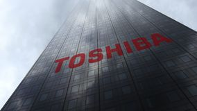Toshiba Corporation logo on a skyscraper facade reflecting clouds. Editorial 3D rendering. Toshiba Corporation logo on a skyscraper facade reflecting clouds Royalty Free Stock Photo